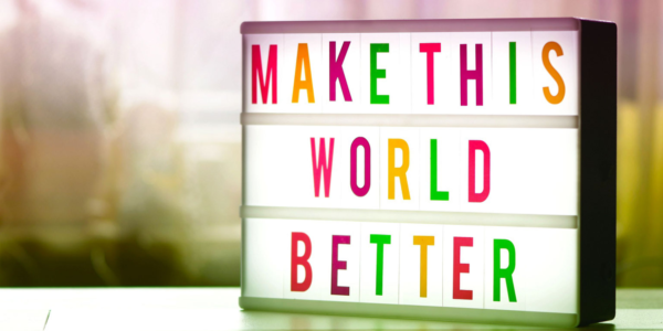 """Header image for policy blog. Sign that says """"Make This World Better"""""""